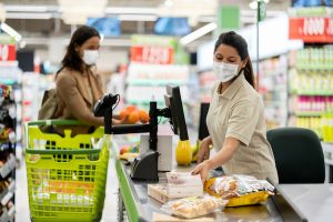shier scanning products at a grocery store wearing a facemask