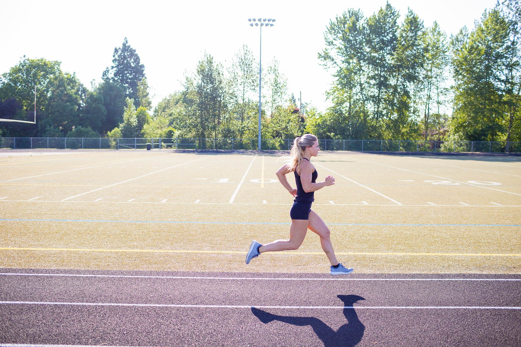 Female runner performs short sprints while working out on an outdoor track in the summer.