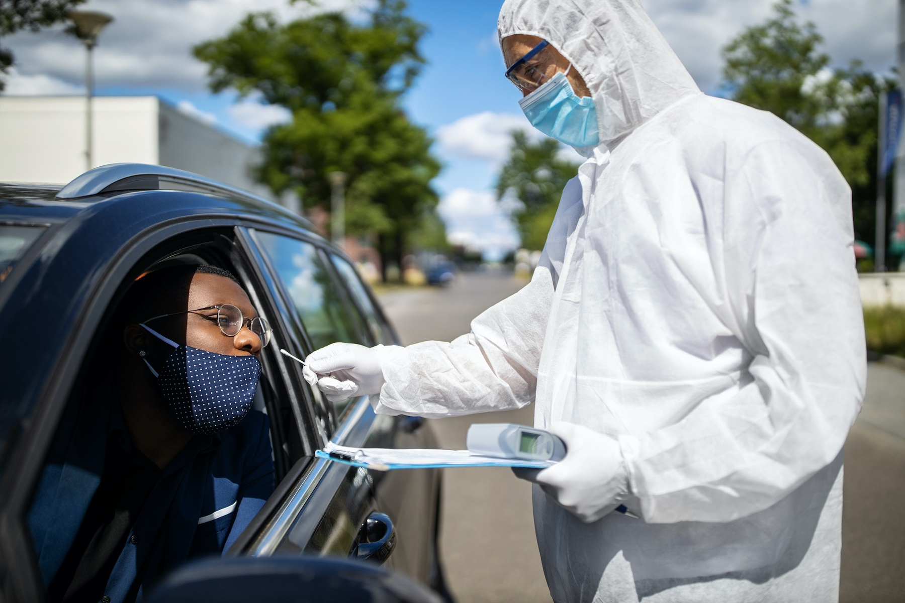 Doctor in a protective suit taking a nasal swab from a person to test for coronavirus infection.