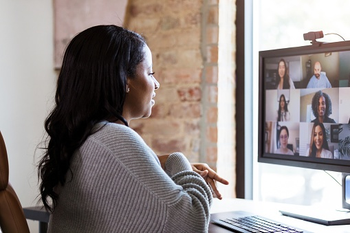 A woman uses video conferencing to meet with her colleagues.