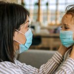 Mother putting protective mask on her daughter's face