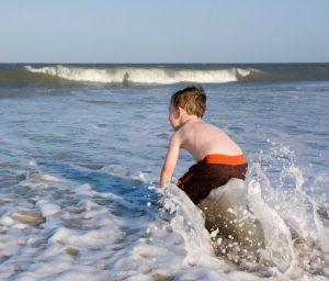 Boy playing in ocean surf